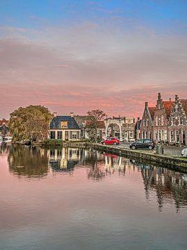 Zonsondergang tussen de bomen in het Friese havenstadje Makkum van
