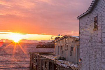 Sonnenaufgang beleuchtet ein altes Holzhaus am Meer in Henningsvaer, Lofoten, Norwegen von Sander Groffen