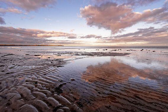 Küstenlandschaft mit Sandrippen und farbigen Wolken