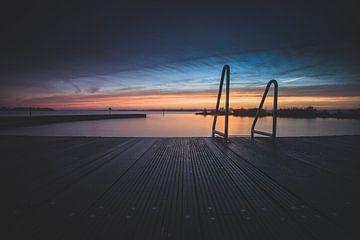Open lucht zwembad aan recreatieplas tijdens zonsondergang van