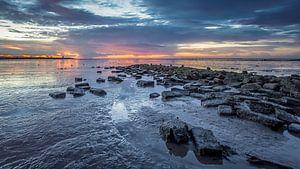 Stenen aan de Waddenzee tijdens zonsondergang van
