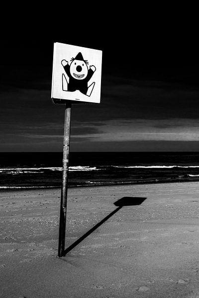 Schwarz-Weiß-Bild eines Schildes mit einem Clown am Strand von Wim Stolwerk