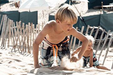 jongens spelen in de zomer in het zand van Kim Groenendal