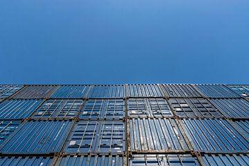 Mooie blauwe zeecontainers gestapeld tegen een mooie heldere blauwe lucht