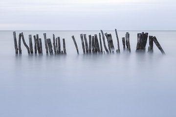 Holzpfähle im Meer während eines stürmischen Abends. Isla Holbox Mexiko. von Sander Hupkes