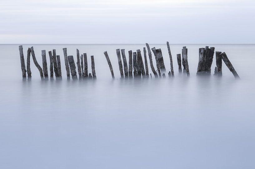 Houten palen in de zee tijdens een stormachtige avond. Isla Holbox Mexico. van Sander Hupkes