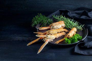 Verse scampi's, ook wel langoustine of langoustine genoemd, met kruiden op een bord op een donkerbla van Maren Winter