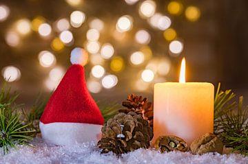 De rode hoed van de Kerstman met kaars en vage lichtenachtergrond van Alex Winter