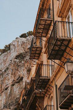 Antike Gebäude mit Balkonen in Cefalu Stadt unter den Felsen, Sizilien Italien. von Manon Visser