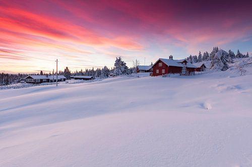 Ondergesneeuwd Noors gehucht na zonsondergang van