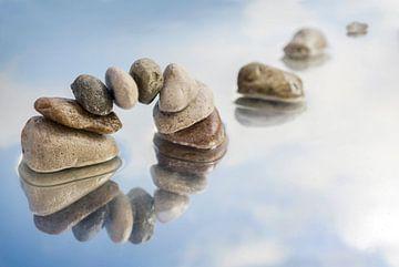 boog van uitgebalanceerde kiezelstenen en stapstenen in het water met reflectie, lichtblauwe lucht m van Maren Winter