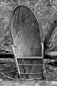 Kapotte rieten stoel bij een verlaten huis van
