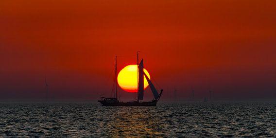 Zonsondergang op het IJsselmeer met een historisch schip als silhouet