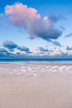Roze wolk boven strand en noordzee op een zomerse ochtend van