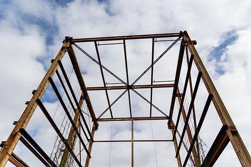 Urbex - verroeste metalen constructie tegen een blauwe lucht met wolken