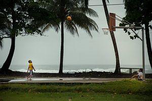 Jongens spelen basketbal naast de Caribische Zee (Costa Rica)