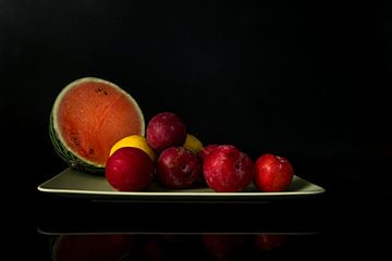 stilleven met een halve watermeloen pruimen en citroenen