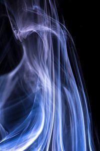 Witte en blauwe rook tegen een zwarte achtergrond