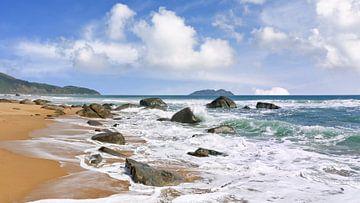 plage tropicale ensoleillée avec des rochers dans une forte ressac sur Tony Vingerhoets