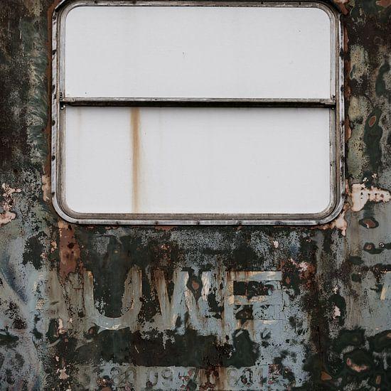 Verweerde oude deur met dicht raam.