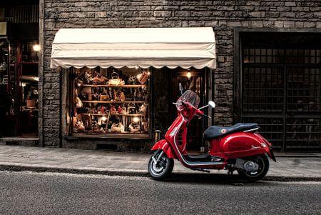 Ein roter Scooter in einem italienischen Straßen