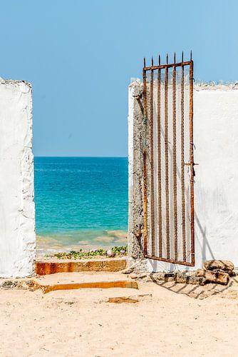 Oude metalen poort naar het strand bij de oceaan in Sri Lanka