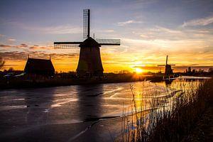 Molen in Alkmaar met ijs op de sloot bij zonsondergang van