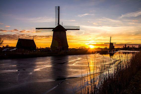 Molen in Alkmaar met ijs op de sloot bij zonsondergang