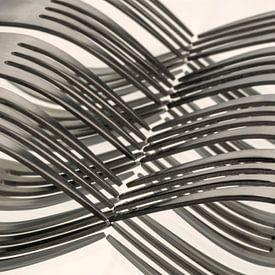 Abstracte artistieke foto van couvert, zijnde vorken welke door spiegeling een golfpatroon vormen van Tonko Oosterink