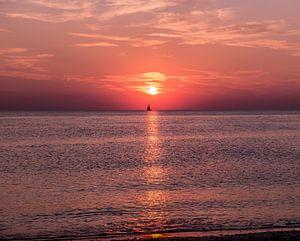 Ondergaande zon met zeilboot van