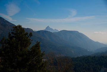Einer nebligen Landschaft mit grünen Bergen und blauem Himmel in Spanien. von Edith van Aken