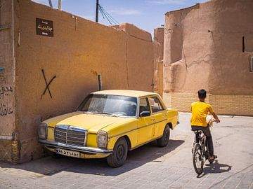 Gele auto in de straten van Yazd, Iran van Teun Janssen