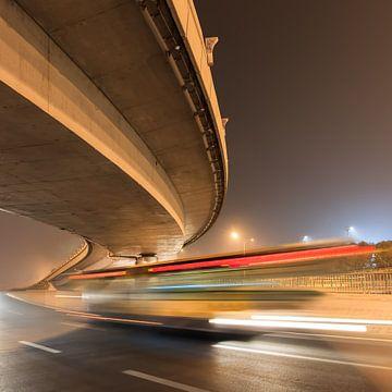 route de courbure élevé avec bus flou de mouvement à la nuit sur Tony Vingerhoets