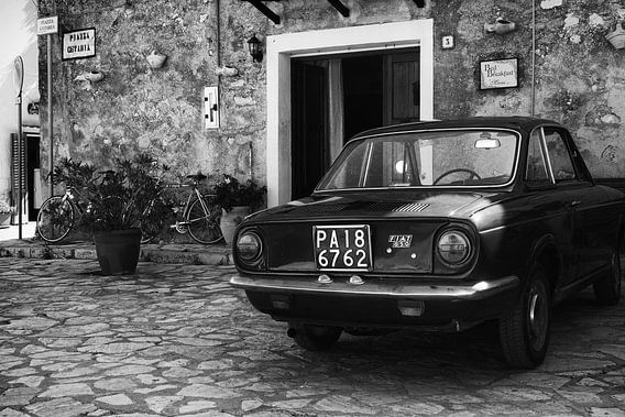 Alter FIAT 850-Oldtimer auf einem Platz in Italien in schwarz-weiß