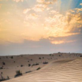 Zonsondergang boven zandduinen in de woestijn van Dubai van Capture the Light