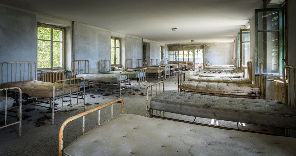 Bedden in een verlaten ziekenhuis van Inge van den Brande