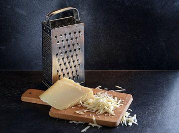 parmezaanse kaas aan stukken en geraspt en een gebruikte metalen rasp op een houten snijplank tegen  van Maren Winter
