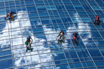 Glazenwassers hangen aan touw terwijl ze de ramen van een glazen wolkenkrabber in Buenos Aires schoo van Wout Kok