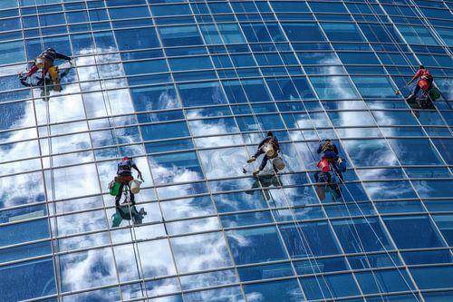 Glazenwassers hangen aan touw terwijl ze de ramen van een glazen wolkenkrabber in Buenos Aires schoo von Wout Kok