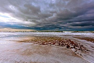 donkere wolken boven strand en zee van eric van der eijk