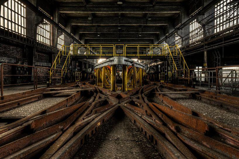 Symmetrische rails met lichtval in verlaten fabriek van Sven van der Kooi