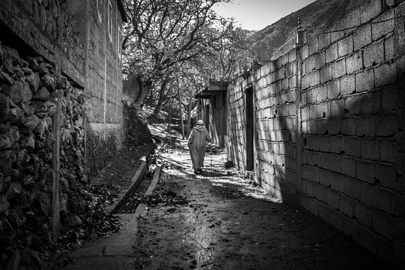Berber man walking through the village van Dick Hooijschuur