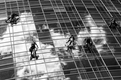 Glazenwassers hangen aan touw terwijl ze de ramen van een glazen wolkenkrabber in Buenos Aires schoo