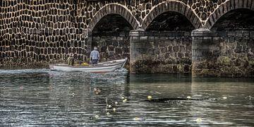 Klein vissersscheepje vaart richting een historische brug sur Harrie Muis