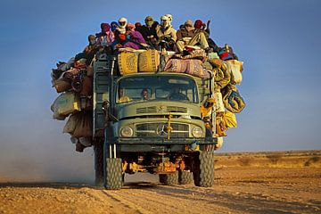 Lastwagen mit Menschen in der Wüste Sahara von Frans Lemmens