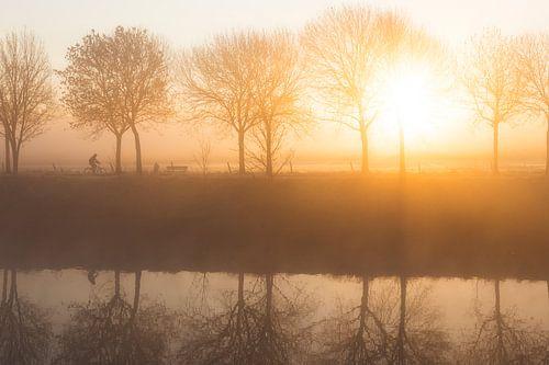 Fietser langs de rivier Leie tijdens een mistige ochtend in de winter met prachtige zonsopkomst in M