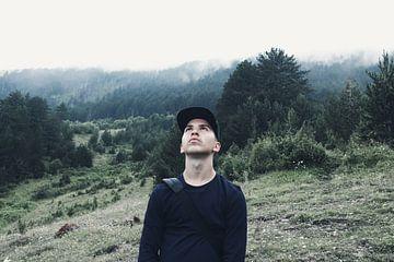 Un jeune randonneur se tient sous la pluie et regarde le ciel nuageux. sur Besa Art