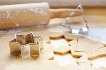 Bakken voor Kerstmis, uitgerold deeg met koekjessnijders in de vorm van een ster en een dennenboom v van Maren Winter