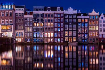 Grachtenpanden aan het Damrak in Amsterdam tijdens het blauwe uur