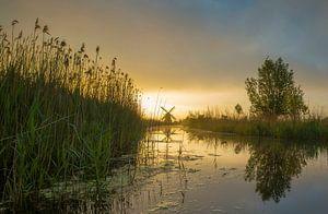 Landschap, zonsopkomst bij molen met weerspiegeling in het water